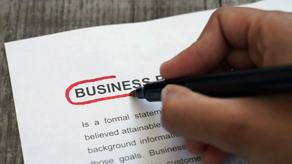 Circling Business Plan with a red marker