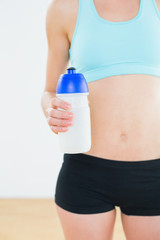 Mid section of a sporty fit woman holding water bottle