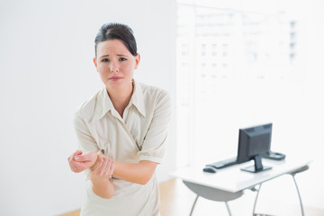 Businesswoman suffering from wrist pain in office