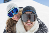 Close-up of a couple in ski goggles against snow