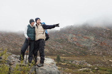 Couple standing on a rock looking at the mountains