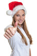 Beautiful woman with christmas hat showing thumb