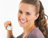 Portrait of smiling woman holding toothbrush with toothpaste