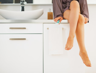 Closeup on toothbrush in hand of young woman sitting in bathroom