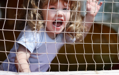 Little beautiful happy girl shouts at playground with grid.