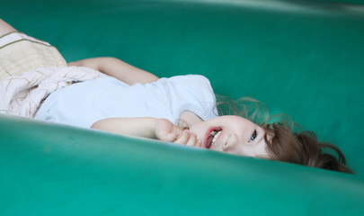Little beautiful happy girl lies on green bouncy castle
