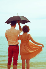 Summer vacation concept. Couple standing on beach near water