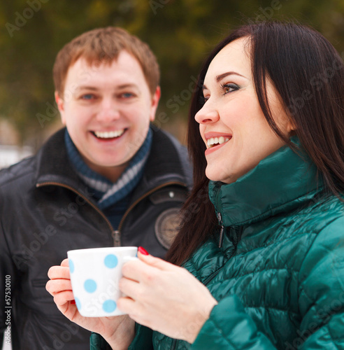Happy couple having fun in the winter park drinking hot tea