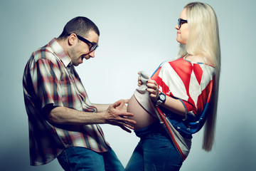 Happy pregnancy concept: portrait of two funny hipsters