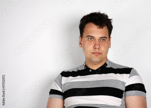 Brunet man in striped T-shirt looks away on grey background.