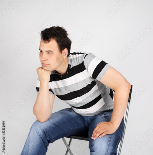 Brunet man in striped T-shirt sits on chair and thinks on grey b