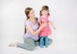 Pregnant woman sits on floor near little smiling daughter on gre