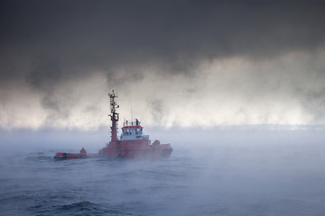Dark image of ship on sea during a violent blizzard.