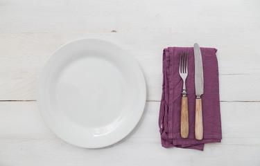 Weisser Teller und Besteck auf hellem Holz