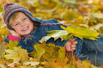 Laughing young girl on the yellow leaves
