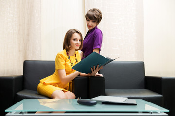 Two young women with a folder at office