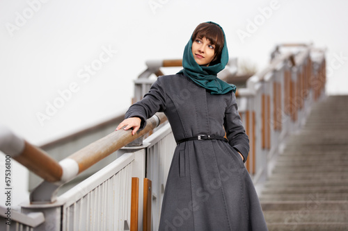 Happy young woman in grey classic coat on the steps