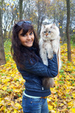 Young woman and  siberian cat in a autumn forest