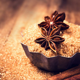 Cinnamon sticks and star anise on cane sugar on wooden backgroun