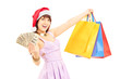 Excited female with santa hat holding shopping bags and dollars