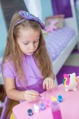 Adorable little girl draws paint in the room