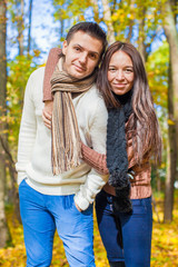 Portrait of Happy couple in love in autumn park on a sunny fall