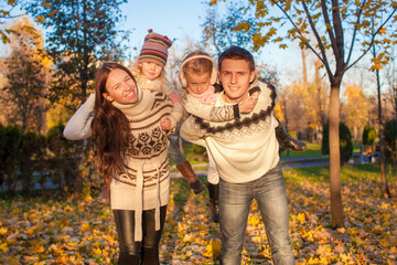 Family of four with two kids having fun in autumn park on a