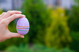 Bright purple Easter egg in hand on background of blue sky
