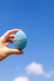 Bright blue Beautiful Easter egg in hand on background of blue