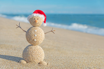 Smiley sandy snowman in santa hat. Holiday concept for New Years