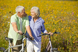 Smiling couple with bicycles among wildflowers in sunny meadow