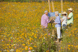 Couples painting on easels among wildflowers in sunny meadow