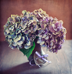 purple hydrangea flowers and a wooden heart on a table.