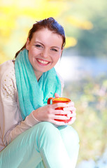 Happy girl relaxing in the autumn park enjoying hot drink