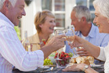 Senior couples drinking wine and enjoying lunch on sunny patio