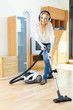 Happy long-haired woman  with vacuum cleaner