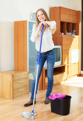 Cheeful woman washing parquet floor with mop