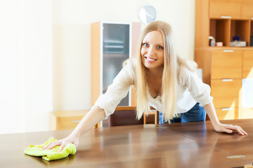 Smiling woman cleaning table at home