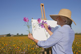 Smiling senior woman painting in sunny wildflower meadow