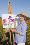 Portrait of smiling senior woman painting in sunny wildflower meadow