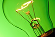 Close up glowing light bulb on green background