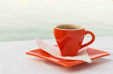 Red coffee cup eith a view of the sea