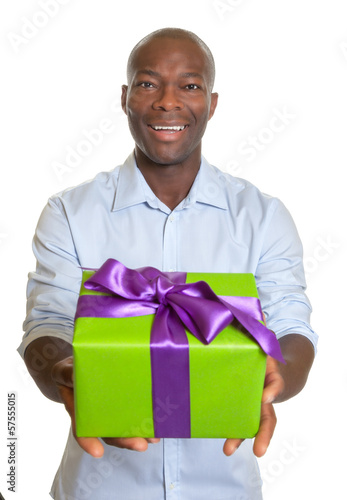 Laughing african man showing a gift for christmas