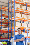 Portrait of smiling worker with arms crossed in distribution warehouse