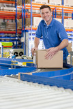 Portrait of smiling worker with cardboard box on production line in distribution warehouse