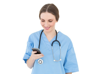 Young woman doctor looking at her smartphone