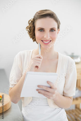 Cheerful woman thinking while writing the shopping list in her k
