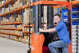 Portrait of smiling worker leaning on forklift in distribution warehouse