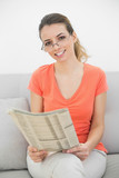 Beautiful ponytailed woman holding a magazine sitting on couch poster