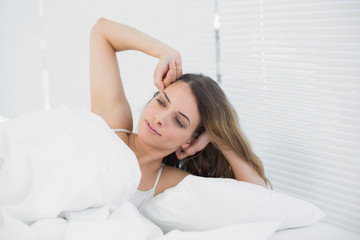 Young brunette woman waking up lying on her bed